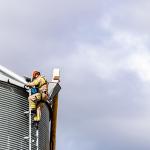 Two firefighters in PPE scaling a grain bin as part of grain bin safety training